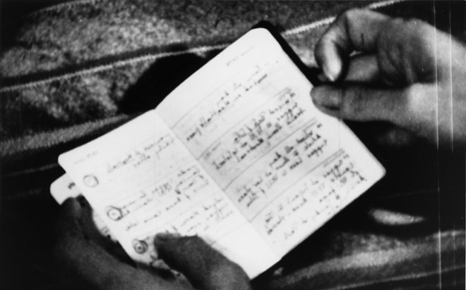 black and white still of hands holding journal