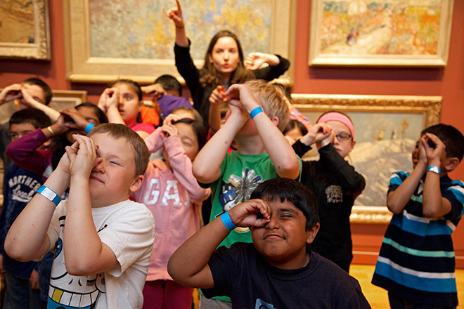 children in the gallery pointing at artworks