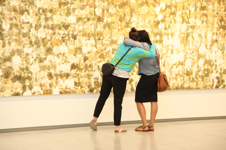 people hugging in front of art