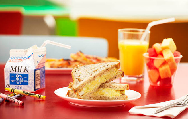 Photo of cafeAGO kids' meal, including sandwich, milk, fruit cup and crayons for colouring