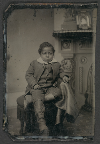 Tintype of unidentified boy with boots