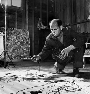 Artist Jackson Pollock dribbling sand on painting while working in his studio.
