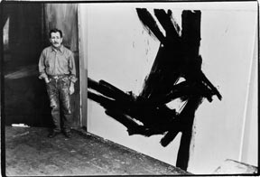 Portrait of American painter Franz Kline (1910-1962) as he poses next to one of his works in his studio (14th Street), New York, New York, April 7, 1961.
