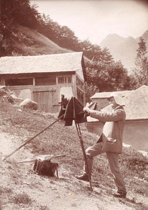 Photograph of a man with a camera standing on a hill with small buildings in the background