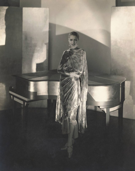 Marion Morehouse wearing a dress by Chéruit and jewelry by Black, Starr and Frost, next to a piano designed by Steichen, 1928