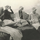 On George Baher's yacht: June Cox wearing unidentified fashion; E. Vogt wearing fashion by Chanel and a hat by Reboux; Lee Miller wearing a dress by Mae and Hattie Green and a scarf by Chanel; Hanna-Lee Sherman wearing unidentified fashion, 1928.