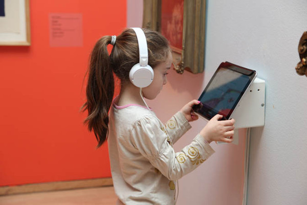 young child holding a tablet in gallery