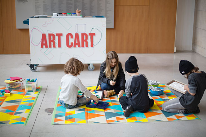 Child making art on mat in front of Art Cart