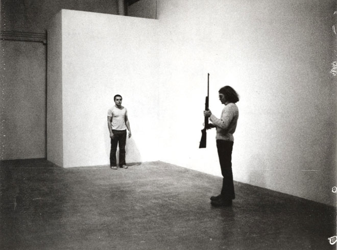 person looking at another person standing with rifle