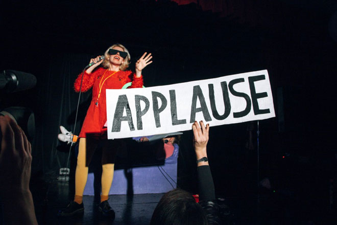 person holding up applause sign at performance